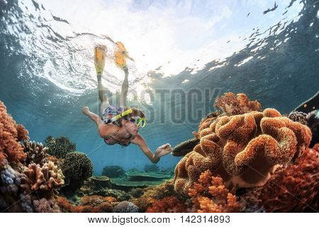 Young woman snorkeling over coral reef in the tropical sea.