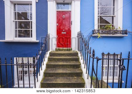 Traditional entrance of a British blue painted house with red door at Notting Hill district near Portobello road - London, UK