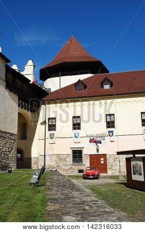 KEZMAROK SLOVAKIA - JULY 08 2016: The old tower and red english car in Kezmarok castle High Tatras Slovakia.