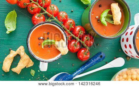 Hot tomato soup in rustic enamel mug