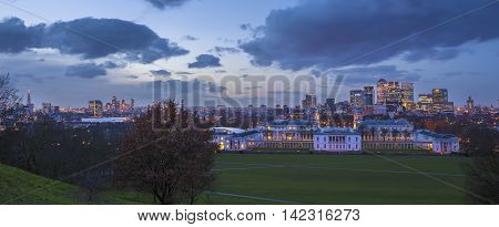 Skyline view of London with National Maritime Museum and skyscrapers of Canary Wharf from Greenwich park at dusk, blue hour - London, UK
