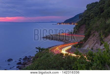 Chalerm Burapha Chonlathit highway along a sea at Noen Nangphaya view point with a light from a car in an evening