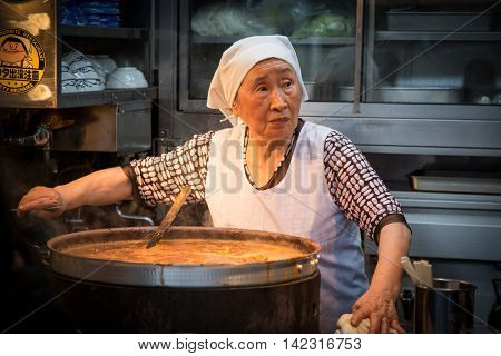 TOKYO, JAPAN - June 24 2016: Tsukiji Fish market in Tokyo. Elderly woman prepares hot street food in large pot.