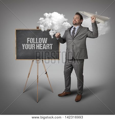 Follow your heart text on blackboard with businessman and paper plane