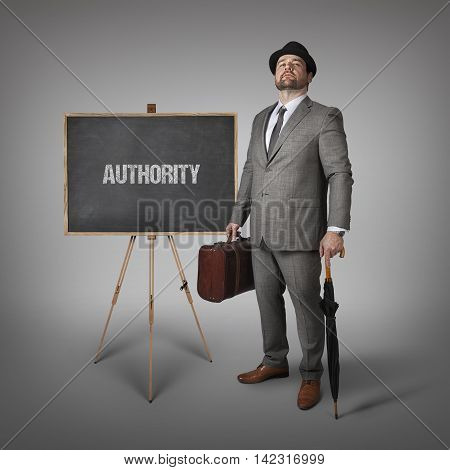 Authority text on  blackboard with businessman holding umbrella and suitcase