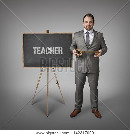 Teacher text on  blackboard with businessman and key