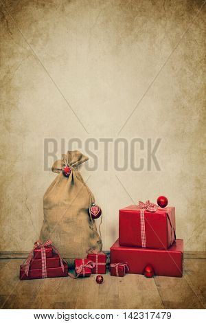Old vintage christmas background with the sack of santa and red gifts for decorations.