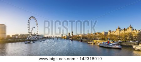 London's skyline view at sunrise with famous landmarks, Big Ben, Houses of Parliament and ships on River Thames with clear blue sky - England, UK