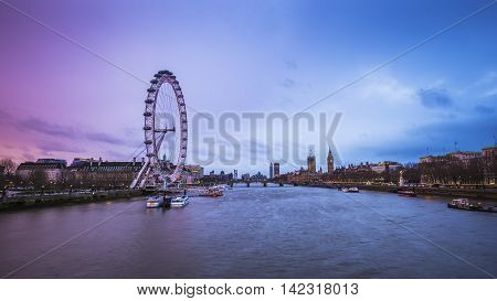 London's skyline view at dusk with famous landmarks, Big Ben, Houses of Parliament and ships on River Thames with beautiful blue and purple sky - London, UK