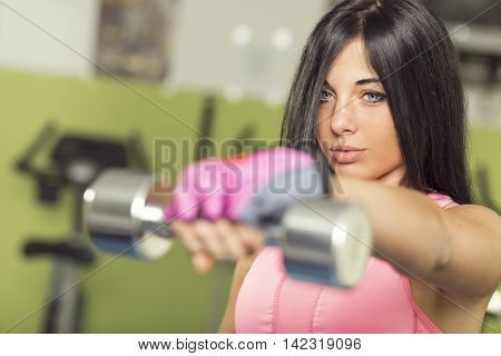 Attractive muscular young woman working out in a gym lifting weights