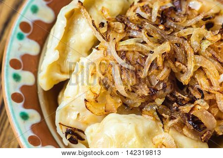 Dumplings with meat and onions. Selective focus. Close up fresh boiled dumplings with hot steams on ceramic plate. Chinese food on rustic old vintage wooden background.