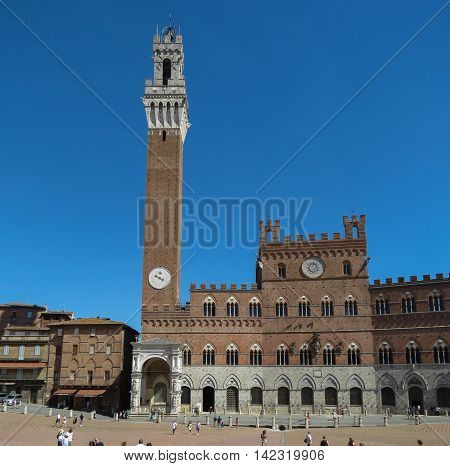 Medieval town hall with the Mangia tower and Piazza del Campo in Siena Italy