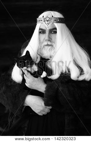 Druid old man with long grey hair and beard with crown in fur coat holds cat black and white on dark background