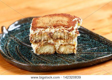 Tiramisu cake on decorated plate on the wooden board