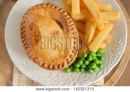 Savory meat pie with chips and peas top down view
