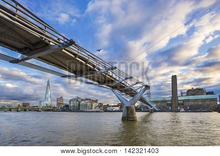 Millennium Bridge on River Thames with beautiful blue sky and clouds, Shard and museum at the background - London, UK