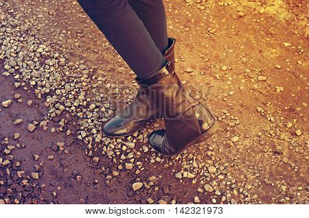 feet in boots on a stone road retro toning