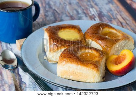 Freshly baked buns with apricot jam on an old metallic a plate and a mug of of tea on a wooden table.