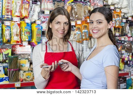 Saleswoman Accepting Card Payment From Female Customer In Pet St