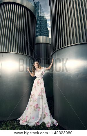 Full growth portrait of fashionable woman in fluttering long dress on urban background