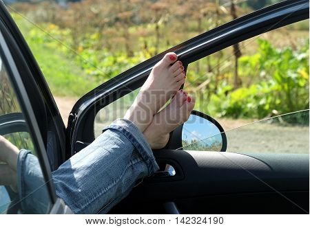 Female feet in jeans rolled up resting placed on opened car door outdoor in rural place in sunny summer day horizontal view