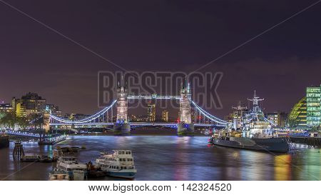 London, England - The Iconic Tower Bridge and HMS Belfast cruiser ship on River Thames by night