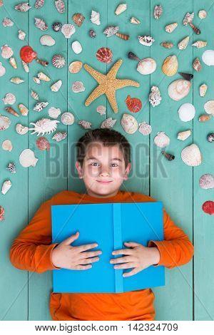 Boy With Blank Book Laying Down Near Sea Shells