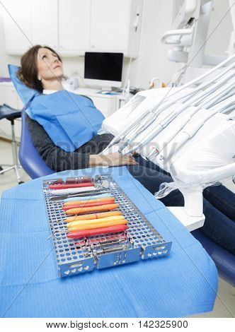 Dental Tools On Tray With Female Patient Sitting On Chair
