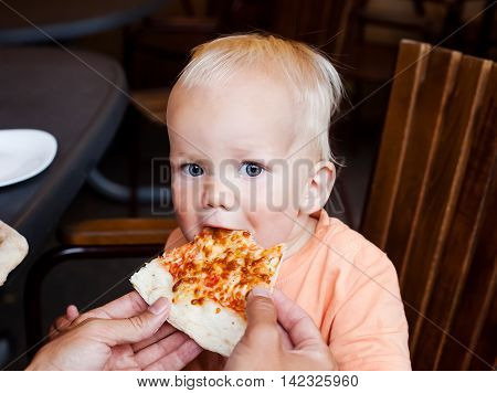 Adorable child toddler boy eating pizza slice at a restaurant summertime. Looking at the camera. Surprise of eyes.