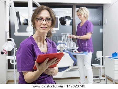 Assistant Holding Digital Tablet While Colleague Working At Dent