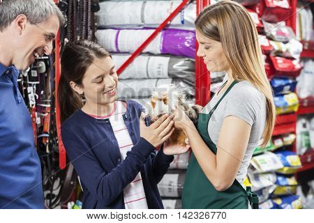 Saleswoman Giving Guinea Pig To Girl At Store