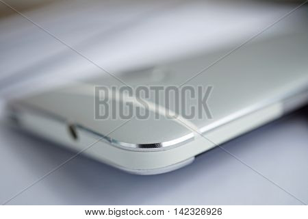 Macro detail of a silver brushed aluminum texture of sleek modern smart phone with shiny beveled edges