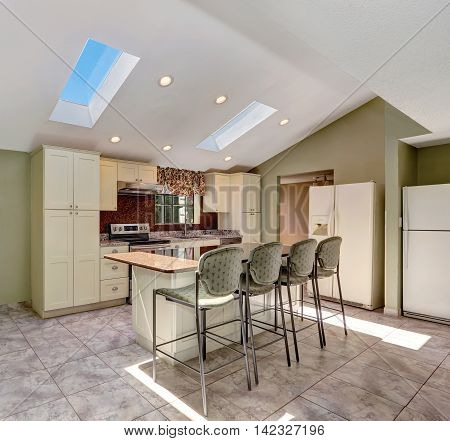 Bright Sunny Kitchen With Vaulted Ceiling And Skylights.