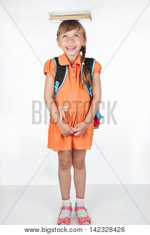Schoolgirl with a textbook on her head, standing on a white background