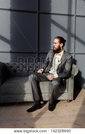 Handsome strong brutal bearded man sitting on the grey sofa in hotel room