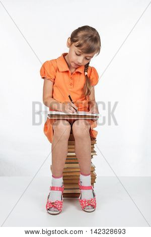 Schoolgirl sitting on the books and writing in a notebook sitting on a white background