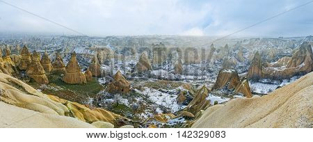 In winter the Pigeon Valley boasts tiny areas covered with green grass and another are covered with snow Cappadocia Turkey.