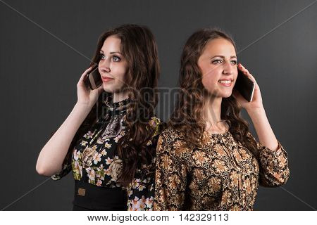 Call me. Two girlfriends talking on the phone, on a gray background