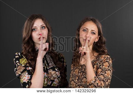 Two girlfriends are asked to be silent, do not tell anyone, on a gray background