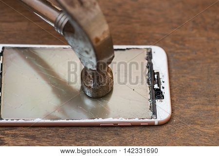 Close up of crash mobile phone smash by rusty iron hammer on wooden table.