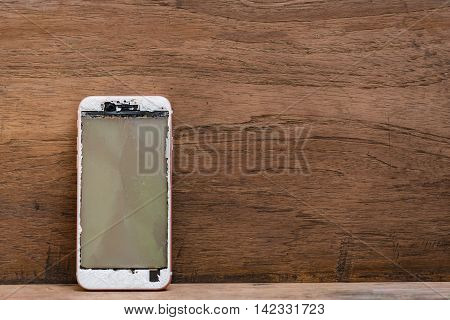 Close up of crash mobile phone on wooden table.