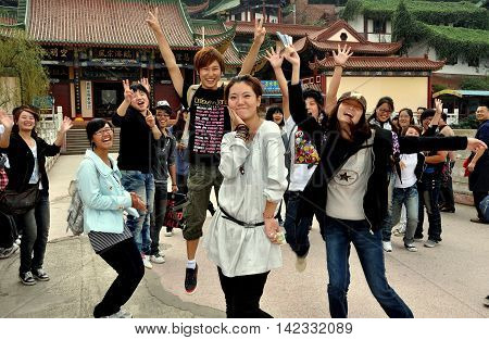 Mianyang China - October 15 2010: Exuberant university students at the entrance bridge pavilion to the Sheng Shui Buddhist temple