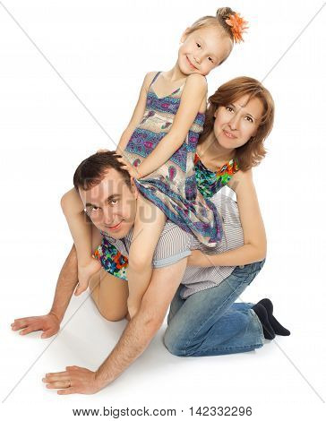 Father , mother and little daughter playing on the floor. Daughter and mom sat in dad's back while dad depicts a horse-Isolated on white background