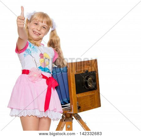 Beautiful little girl with long blonde ponytails on the head posing with an old camera. The girl held out her hands raised in the Upper thumb . Gesture all is well-Isolated on white background