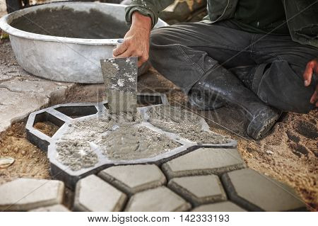 Man pour cement in to a Mold to Make Concrete Pavers