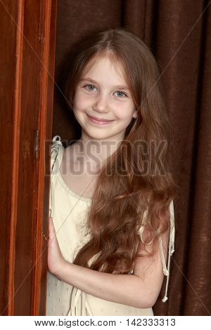 Gentle little girl with long brown hair to her waist . The girl peeks out from behind old closet