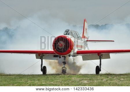Zhitomir Ukraine - May 26 2012: Light trainer and aerobatic plane Yak-52 producing heavy smoke on the airfield after landing