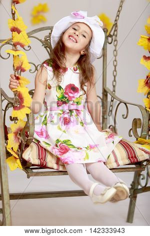 Gentle little girl in a white dress with roses and a white hat. Girl swinging on an old swing. Close-up