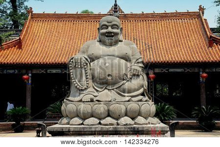 Shi Fang China - June 23 2007: Giant stone Buddha with rotund belly in a courtyard of the historic Luo Han Temple