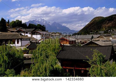 Lijiang China - April 19 2006: View over ancient Naxi homes with tiled roofs to distant Jade Dragon Snow Mountain